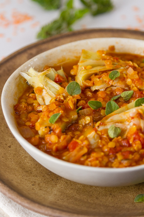 Simple Red Lentil and Artichoke Stew in a tan bowl on a brown plate with red lentils and oregano in the background
