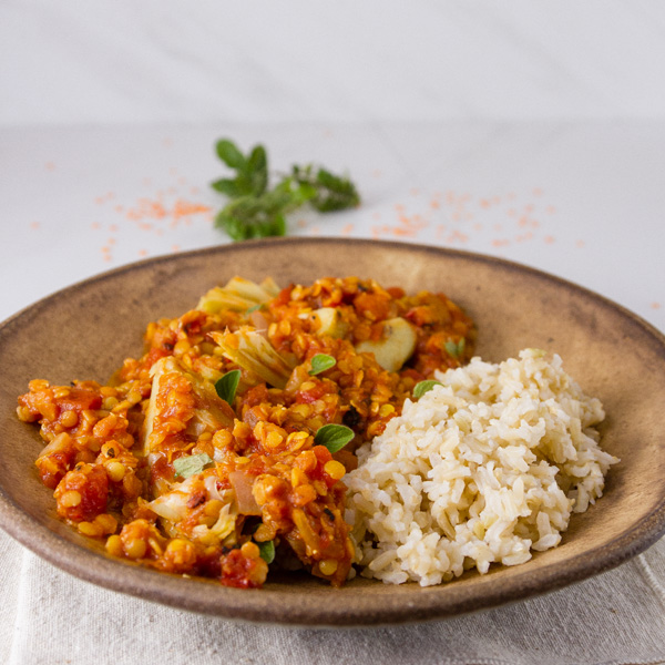 Red Lentil and Artichoke Stew with brown rice in a brown bowl