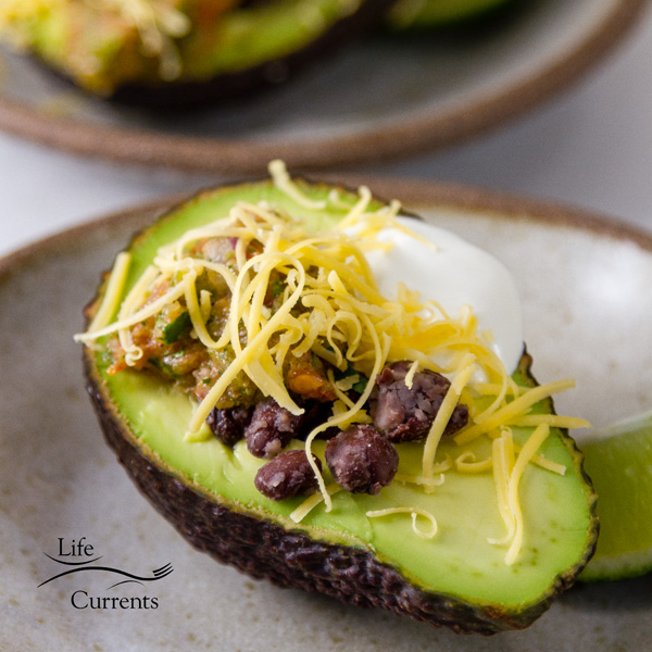 Square crop of 4 Layer Stuffed Avocados on a white plate with a lime wedge