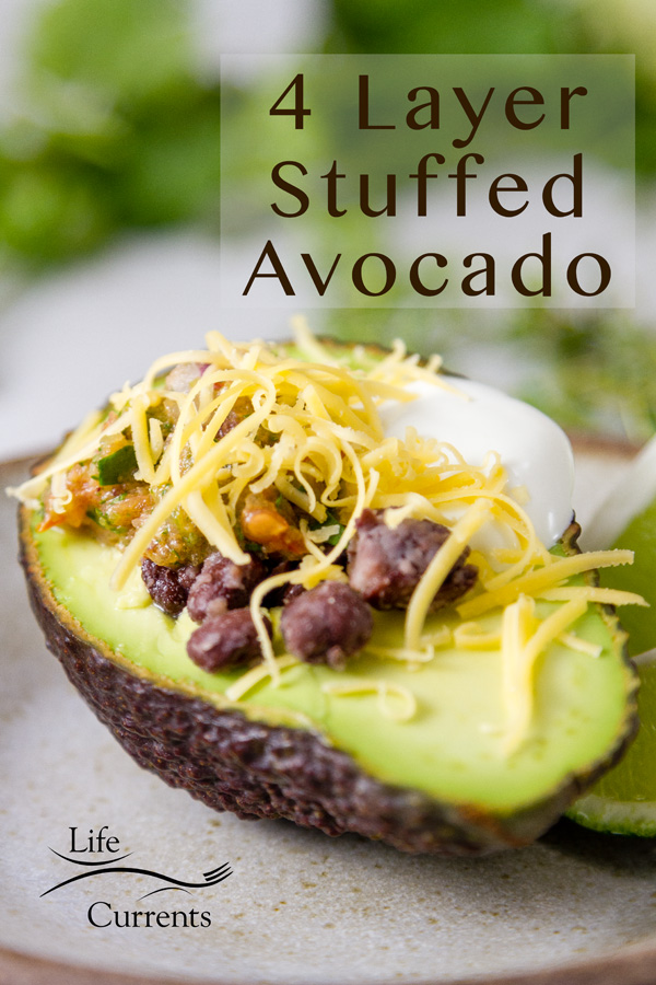 4 Layer Stuffed Avocados on a white plate with cilantro in the background, title added