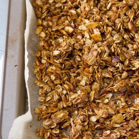 Freshly made Homemade Granola Recipe still in the rimmed baking sheet with the parchment paper