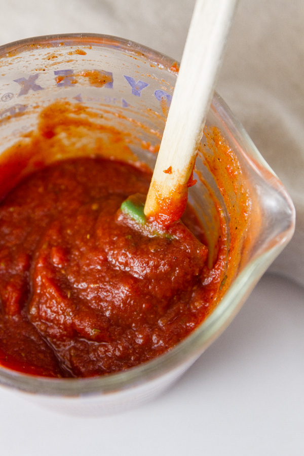 Pizza sauce in a glass pyrex measuring cup with a spoon