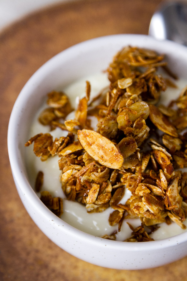 Homemade Granola Recipe served over yogurt in a white bowl on a brown plate