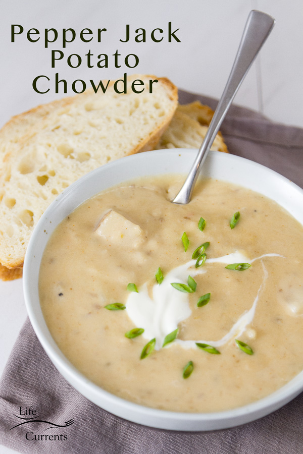 A bowl of Pepper Jack Potato Soup in a white bowl with a grey napkin, spoon in the bowl, and some bread. Title on image