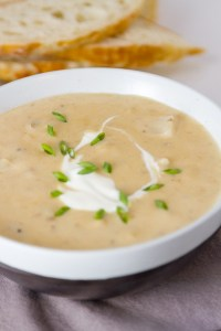 a bowl of Pepper Jack Potato Soup with a sour cream and chive garnish and bread slices in the background