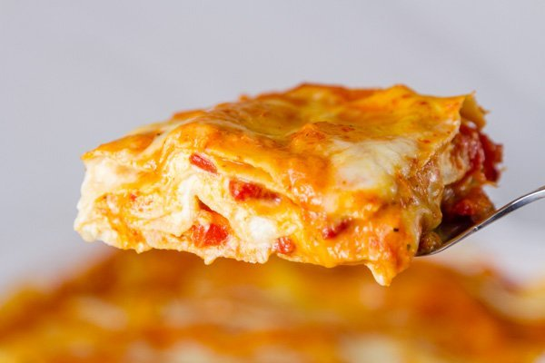 Red Pepper Lasagna one serving on a serving spoon being served up in a side view