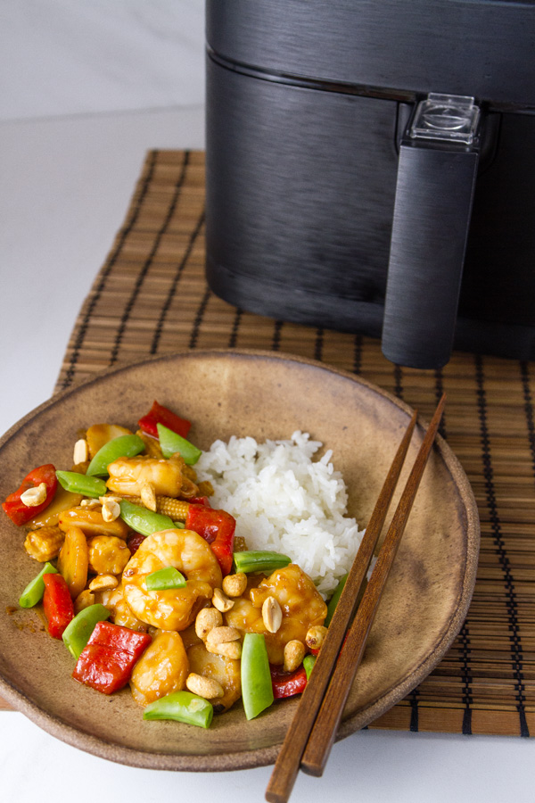 Air Fryer Kung Pao Shrimp in a bowl with rice in front of the air fryer on an Asian mat