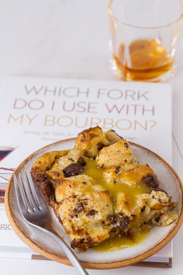 a piece of Chocolate Bread Pudding with Bourbon Butter Sauce with a fork on top of the book, Which Fork Do I Use with My Bourbon? Setting the Table for Tastings, Food Pairings, Dinners, and Cocktail Parties  and a glass of bourbon in the back right