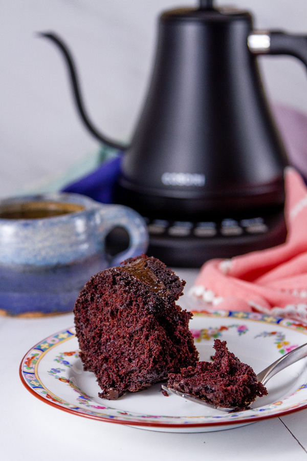 A pice of From Scratch Dark Chocolate Cake on a plate that's been cup into with a fork and the piece is still on the fork. A black kettle and a blue cup of tea in the background