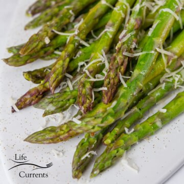 square crop of Foil Packet Grilled Asparagus on a white plate topped with Parmesan cheese