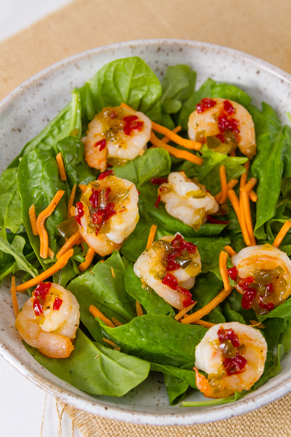 Pepper Jelly Shrimp on a bed of fresh spinach with shredded carrots in a white bowl