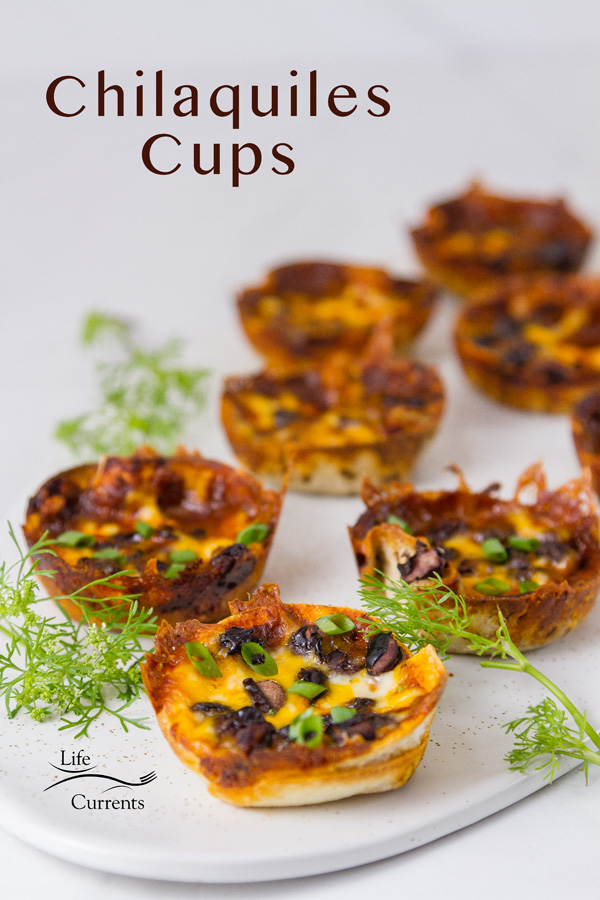 little individual cups made from tortillas and filled with sauce, black beans and cheese. Topped with green onions, and garnished with cilantro on a white platter with the title on the upper left: Chilaquiles Cups