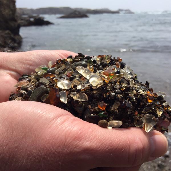 Hands holding beach glass found on Glass Beach