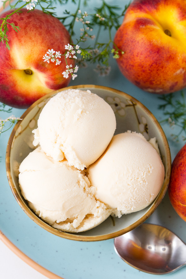 top down looking at a bowl of peach ice cream on a light blue plate with peaches around