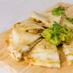square crop of quesadillas on a wooden cutting board served with guacamole and cilantro