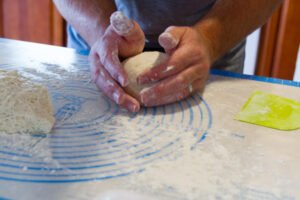 shaping the dough to form a loaf of bread