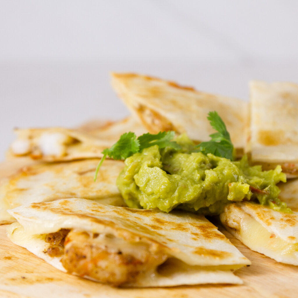 wedges of shrimp quesadillas on a wooden board topped with guacamole and cilantro