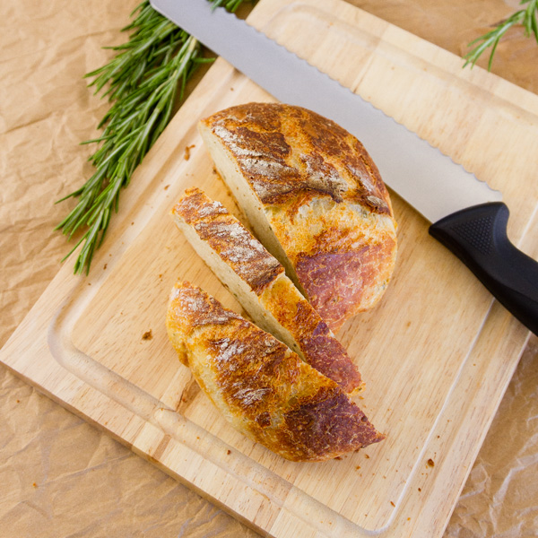 square crop, top down view, No-Knead Parmesan Rosemary Bread with a bread knife on a cutting board