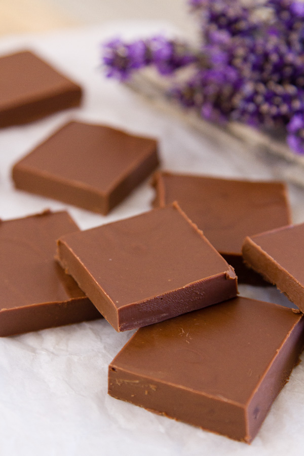 pieces of Two Ingredient Peanut Butter Chocolate Fudge on parchment paper with lavender in the back