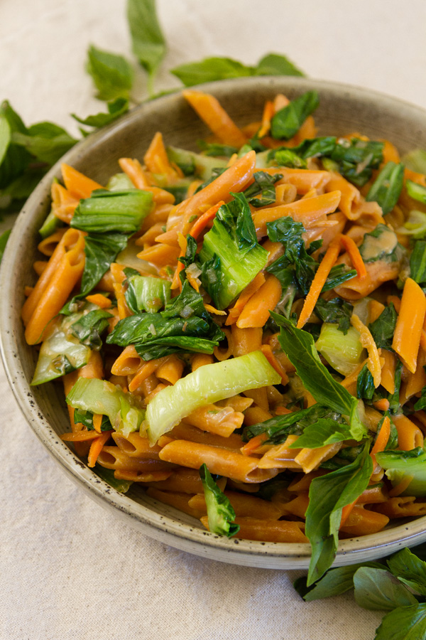 pasta and veggies in a bowl with fresh Thai Basil around it