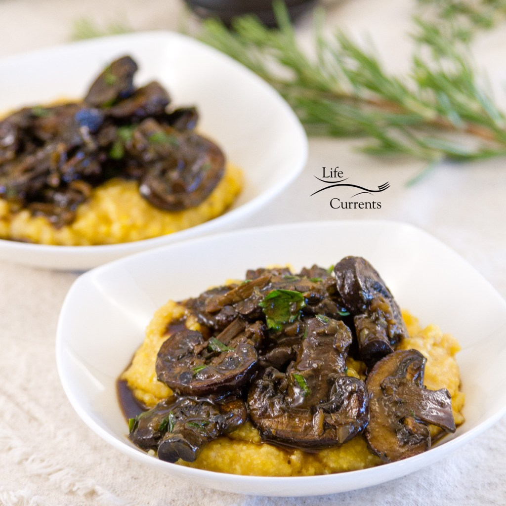 square crop of Mushroom Ragout Over Creamy Polenta in two bowls with fresh rosemary in the background