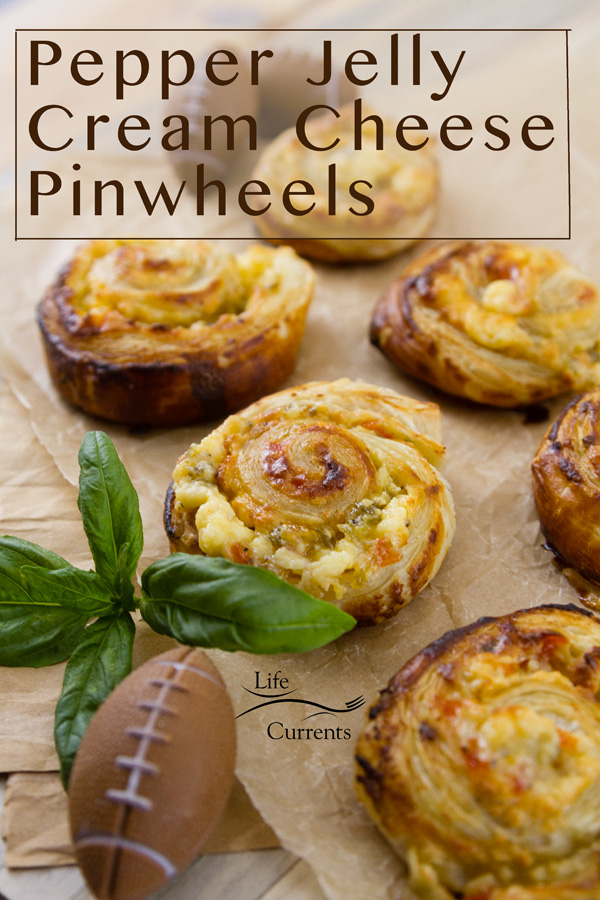 title on image: Pepper Jelly Cream Cheese Pinwheels. Several pinwheels on parchment paper with a small fottball and a sprig of basil