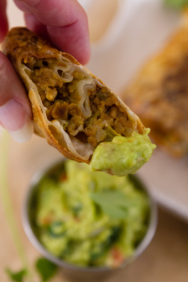 close up of a cut egg roll dipped in guacamole and about to be eaten