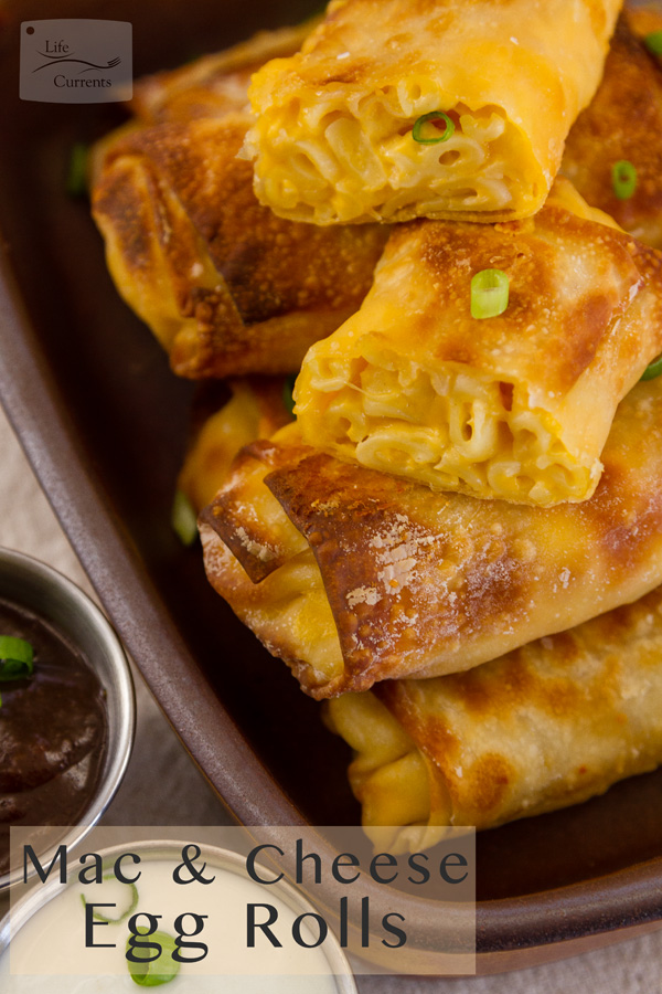 title on lower left: Air Fryer Mac and Cheese Egg Rolls with egg rolls stacked on a serving plate with 2 dipping sauces and green onions around