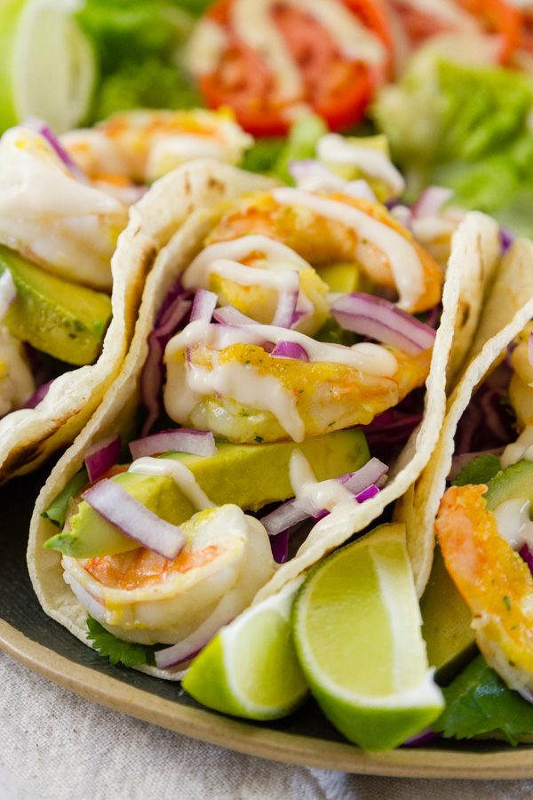 close up on the shrimp in some tacos with lime wedges