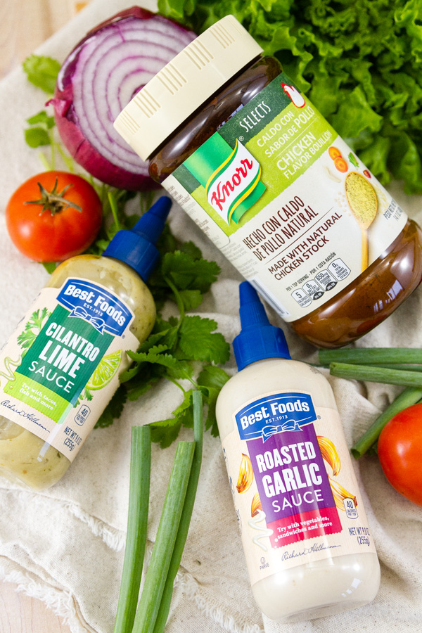 bottles of Best Foods® Drizzle Sauces and Knorr® Bouillon with fresh veggies