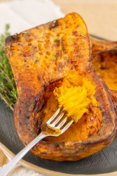 a fork full of roasted butternut squash taken out of the whole cooked squash