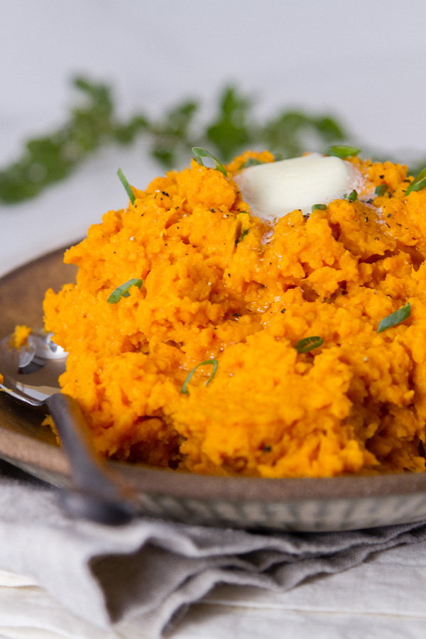 sweet potatoes on a plate with as poon topped with a pat of butter and green onions. Fresh herbs in the background