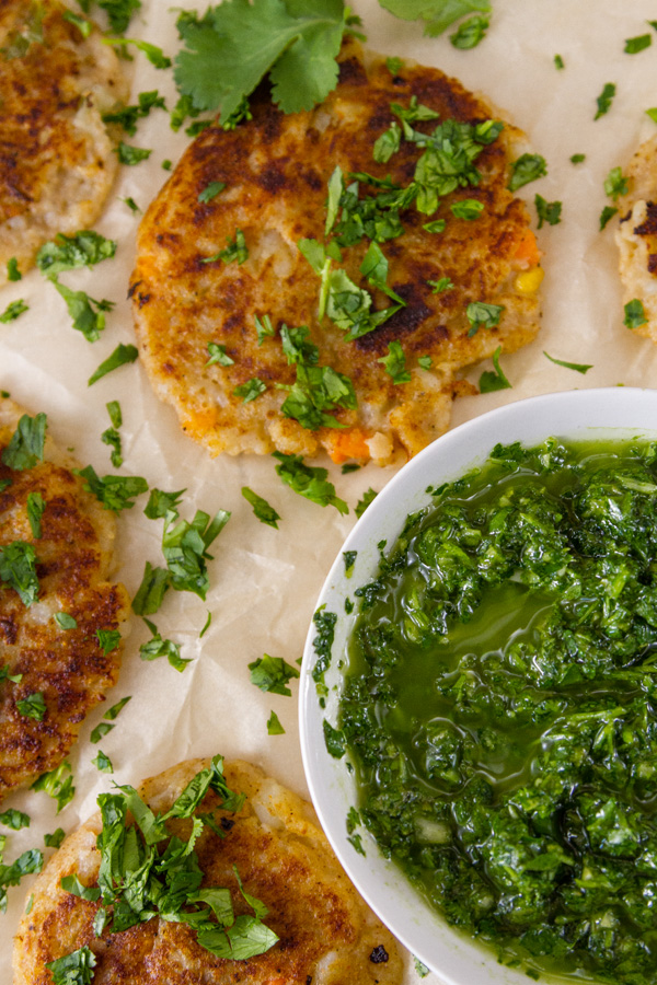 looking down on some cooked fritters served with green Chimichurri sauce, garnished with chopped cilantro.