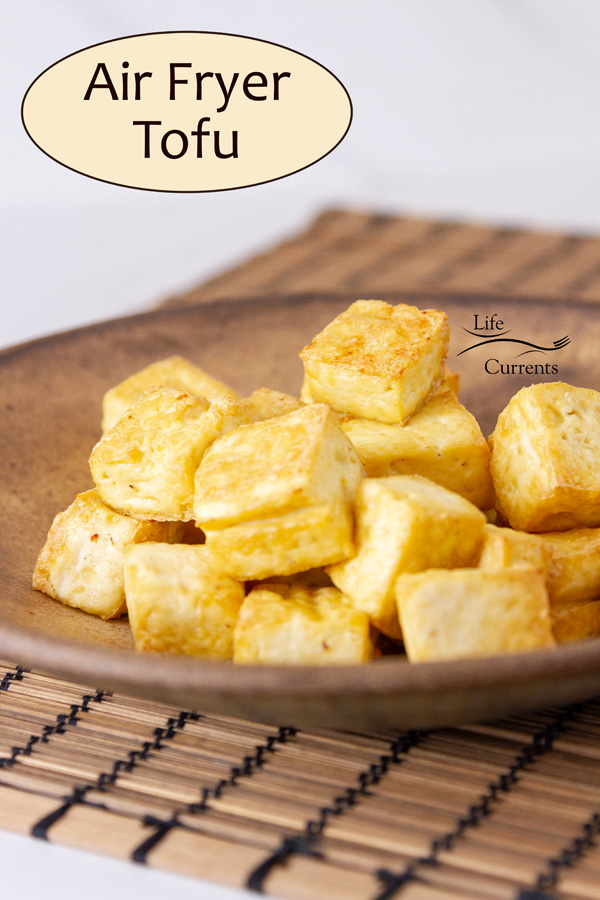 cooked browned tofu on a brown bowl on a mat with title on image: Air Fryer Tofu.