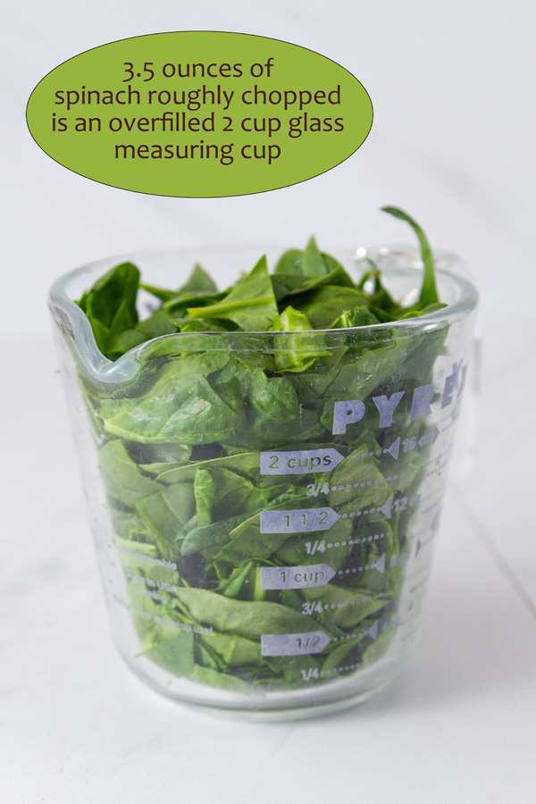 roughly chopped spinach in a glass measuring cup