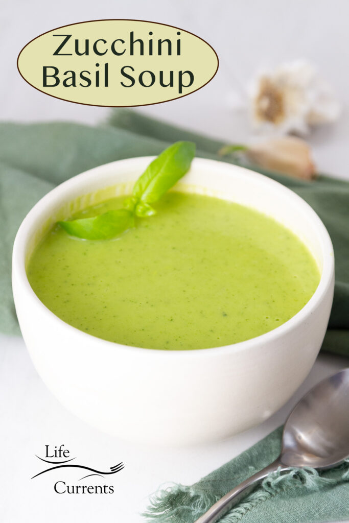 a white bowl with green Zucchini Basil Soup garnished with fresh basil, a spoon next to it, and garlic cloves in the background.