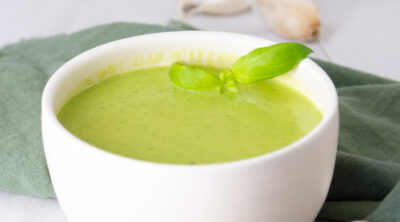 square crop of a white bowl with green soup in it.