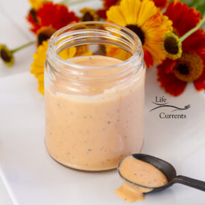 square crop of a jar filled with Comeback Sauce and a black spoon with the sauce on it, flowers in the background.