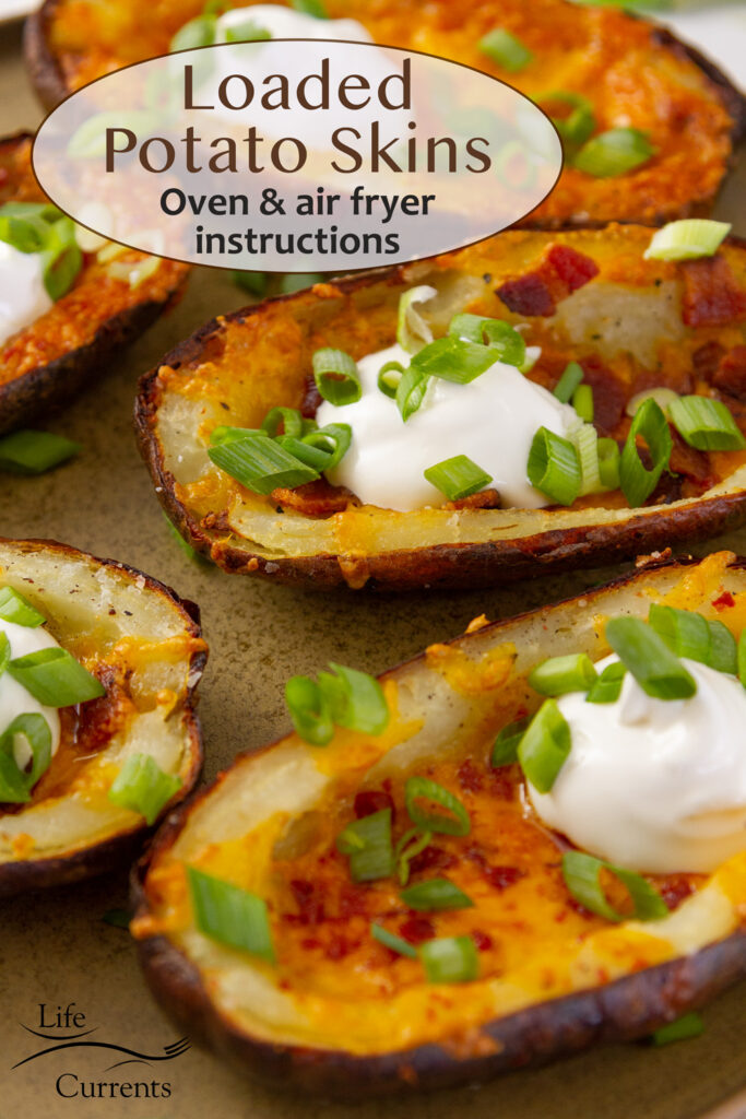 Loaded potato skins with bacon, cheese, sour cream, and green onions on a plate.