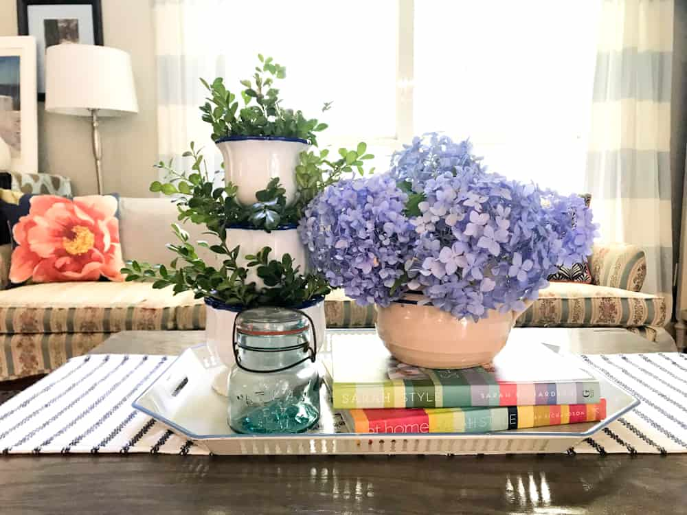 Life Full and Frugal / Summer Living Room Makeover / diy coffee table with vintage tray, blue vintage jar, stacked pottery with greenery and blue hydrangeas arranged in an antique crock pitcher