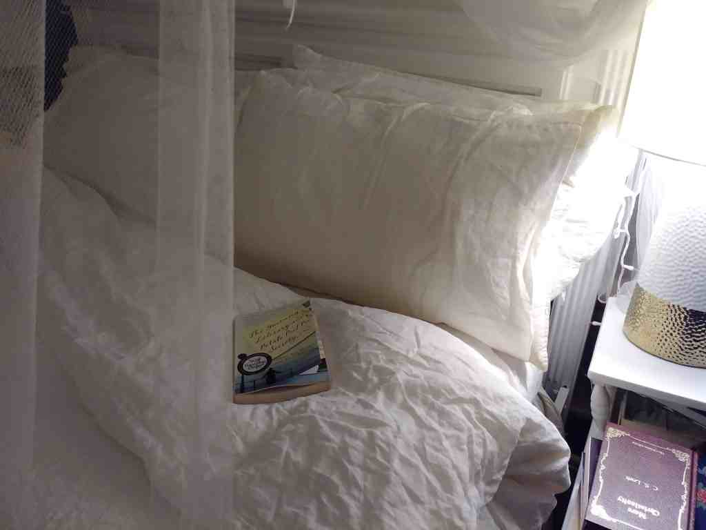 reading a book in a cozy bed with linen sheets life full and frugal