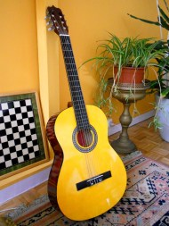 A Spanish guitar rests along the wall