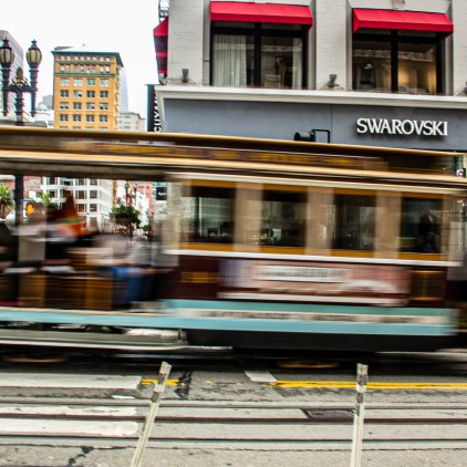 A cable car blurs up Powell St.