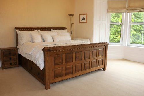 Superking, handcarved wooden bed by Revival Beds in a tidy bedroom.