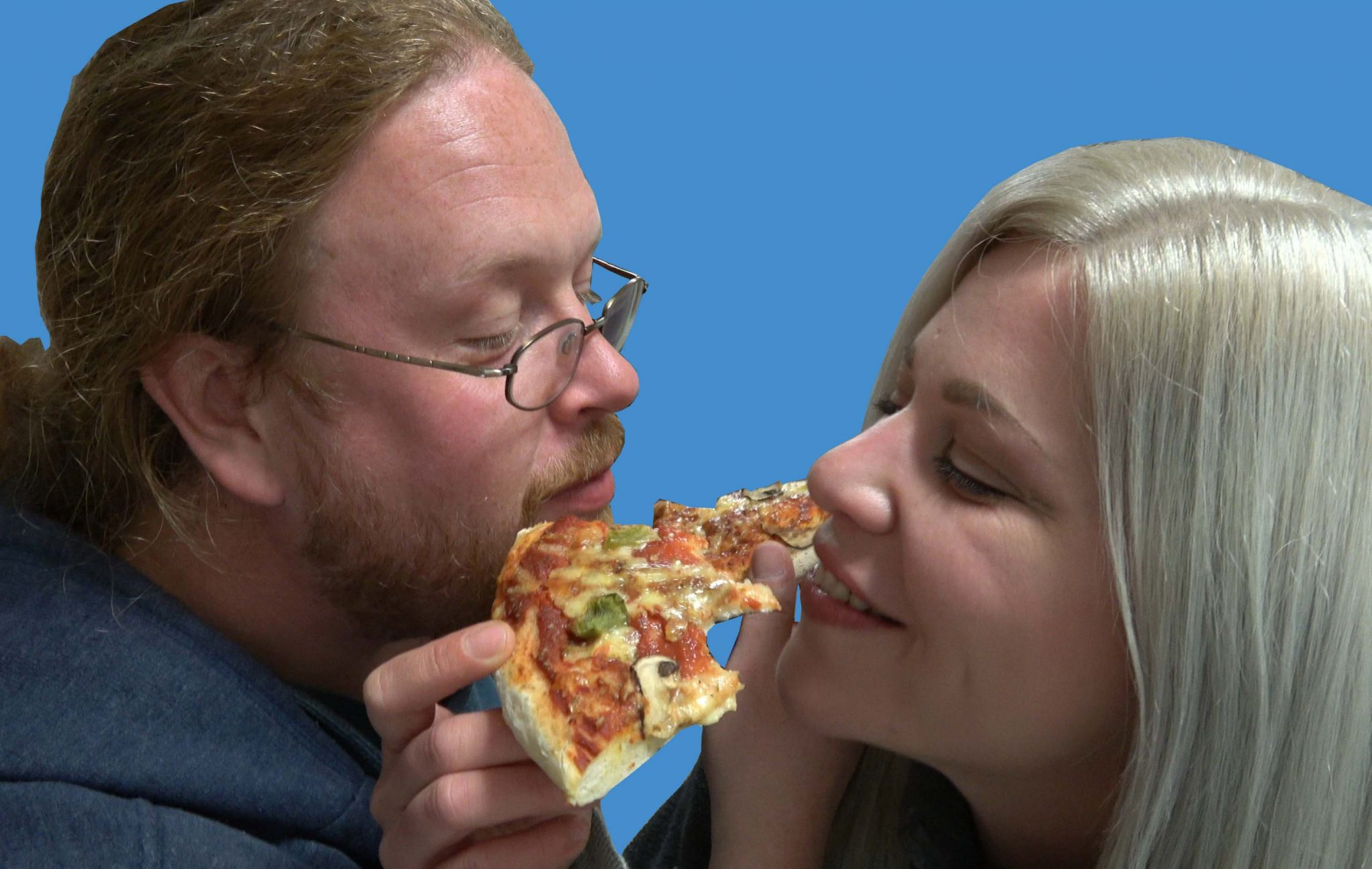 Tim and Christine cross arms to eat their delicious homemade pizza.