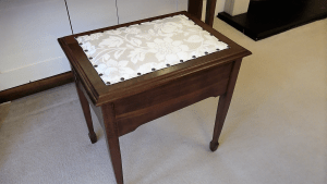 piano stool featuring new fabric and brass studs