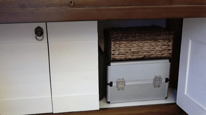 open right hand cupboard of piano dressing table, showing makeup train case and woven basket