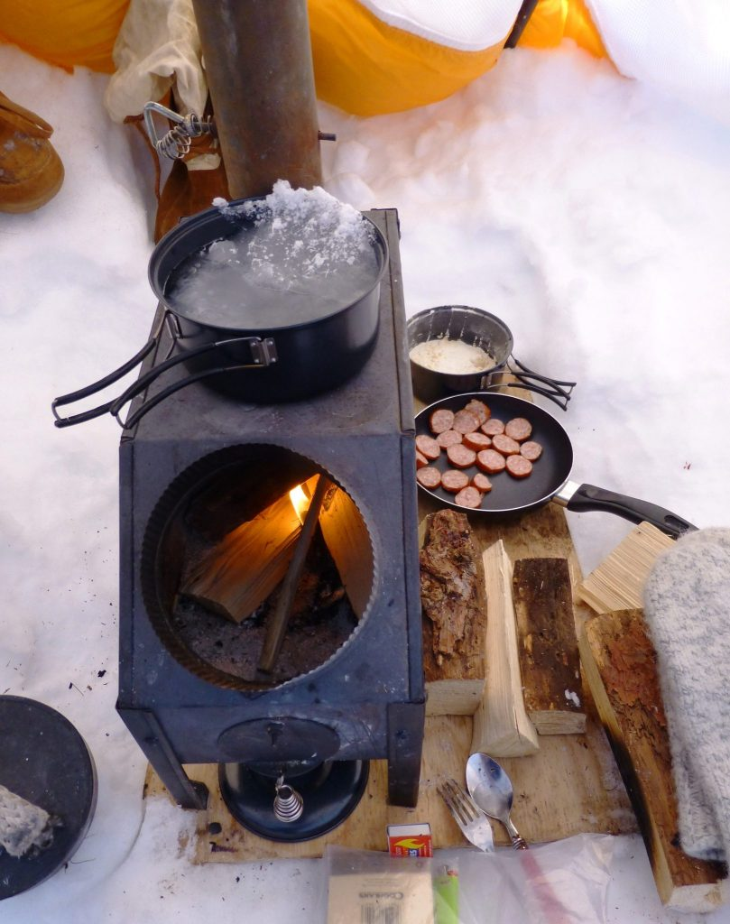 Portable wood burning camping stove melting snow for drinking water during expedition