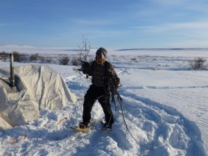 Man on snowshoes collecting firewood during Arctic expedition in Alaska