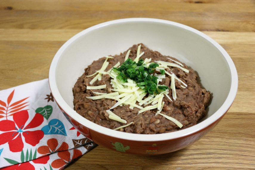 Large bowl of refried beans topped with grated cheese and sliced spring onions